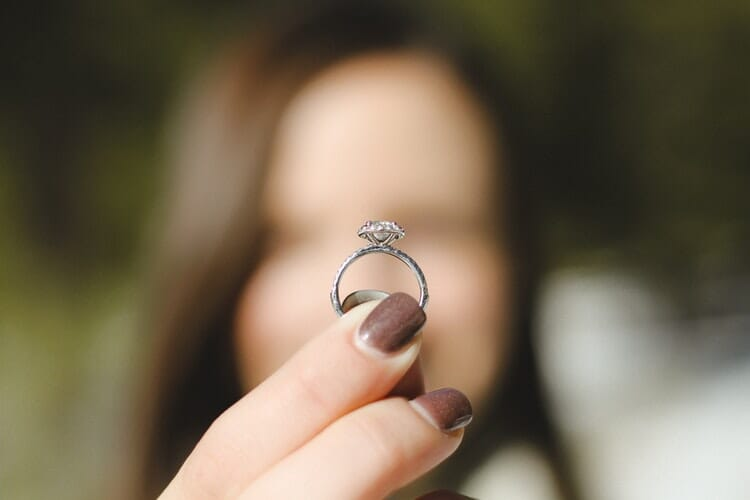 holding a diamond ring